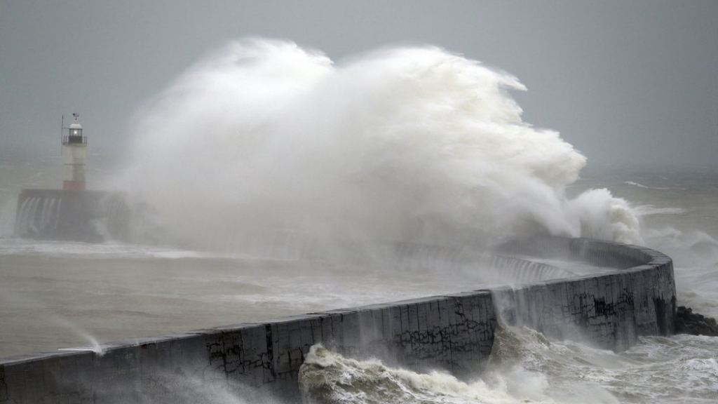 Waves crash into the wall at Newhaven south east England, as Storm Ciara, named by the Met Office national weather agency, hits the UK, Sunday Feb. 9, 2020. Trains, flights and ferries have been cancelled and weather warnings issued across the United Kingdom as a storm with hurricane-force winds up to 80 mph (129 kph) batters the region. (Andrew Matthews/PA via AP)