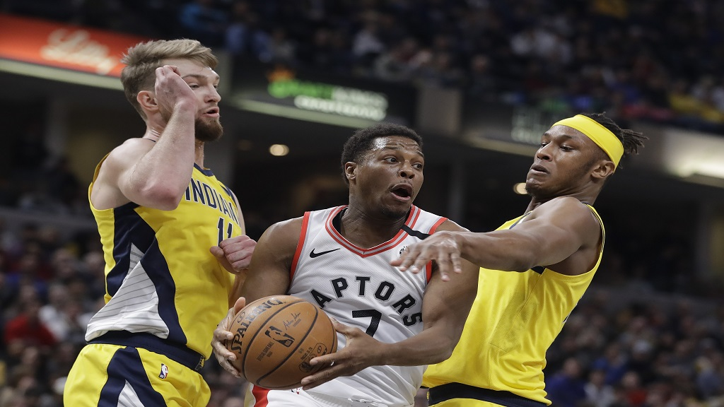 Toronto Raptors' Kyle Lowry (7) makes a pass against Indiana Pacers' Domantas Sabonis (11) and Myles Turner (33) during the first half of an NBA basketball game, Friday, Feb. 7, 2020, in Indianapolis. (AP Photo/Darron Cummings).
