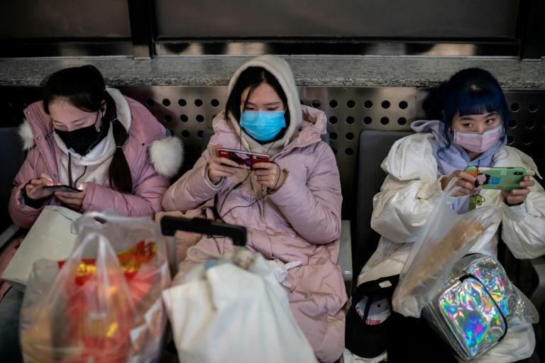 Des voyageurs protégés par des masques sont à la gare de Pékin le 24 janvier 2020 prets à prendre le train pour le nouvel an chinois