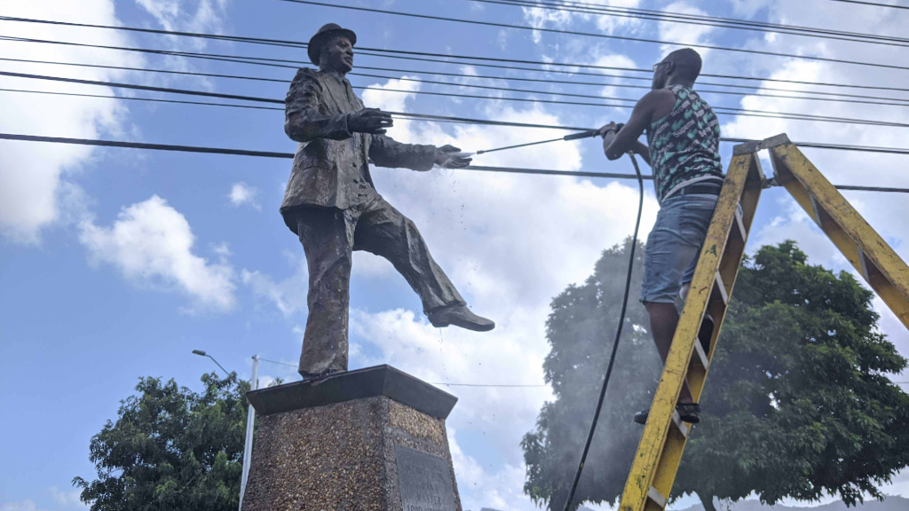 Kernal 'Kitch' Roberts (right), power washes his father's (Lord Kitchener) statue in St James.