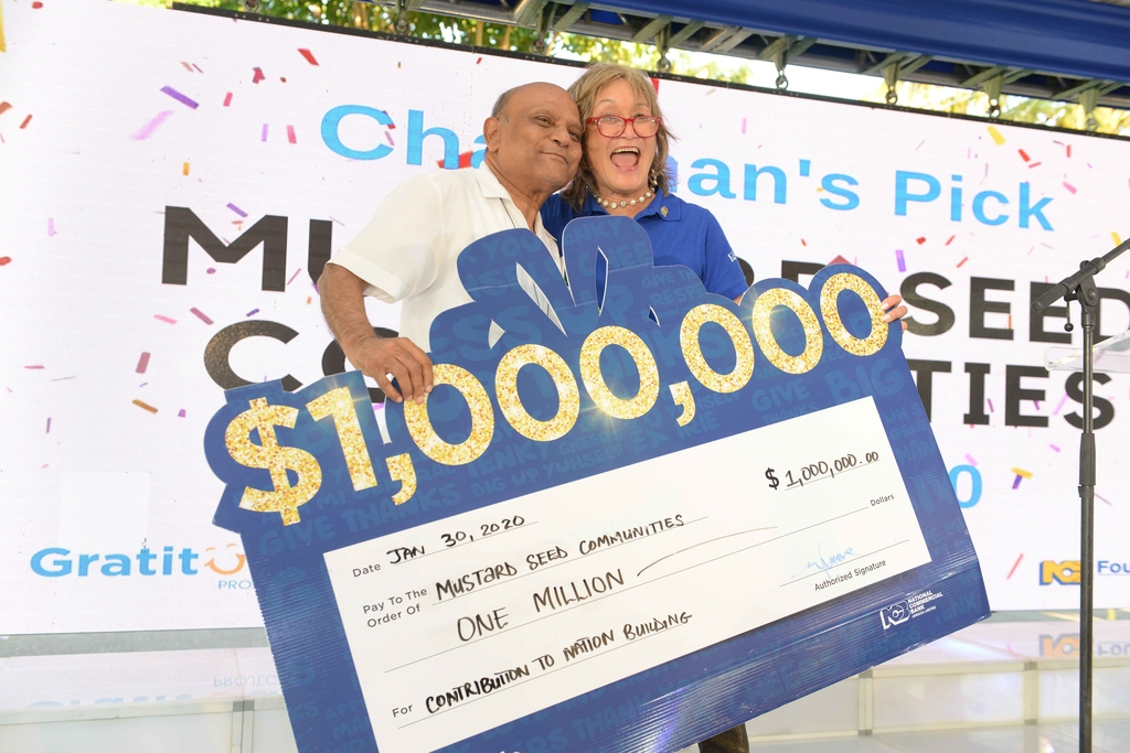 Monsignor Ramkissoon (left), Founder Mustard Seed Communities is all smiles with Thalia Lyn, Chairperson NCB Foundation during the presentation of a $1 million cheque.