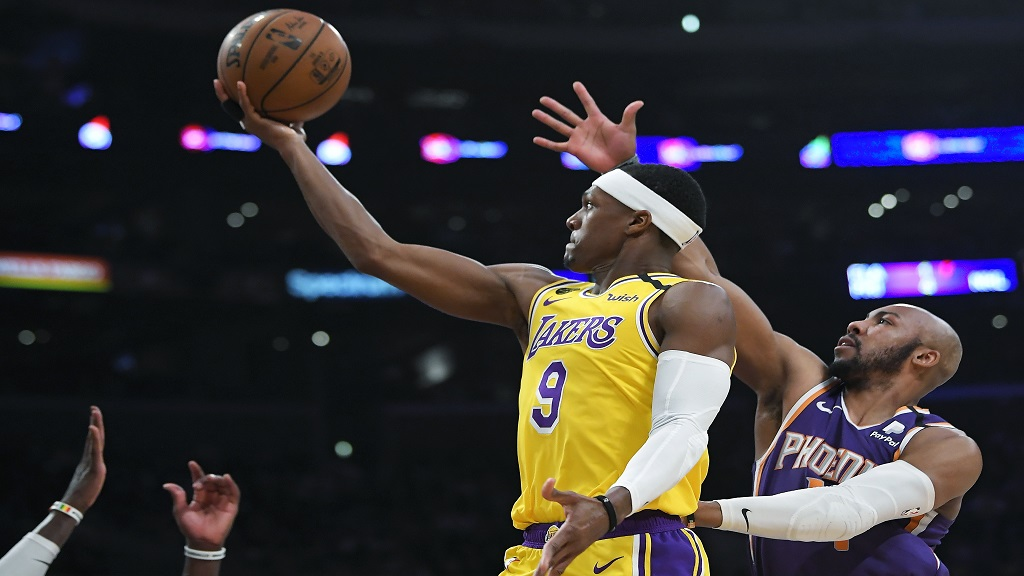Los Angeles Lakers guard Rajon Rondo, left, shoots as Phoenix Suns guard Jevon Carter defends during the second half of an NBA basketball game, Monday, Feb. 10, 2020, in Los Angeles. The Lakers won 125-100. (AP Photo/Mark J. Terrill).