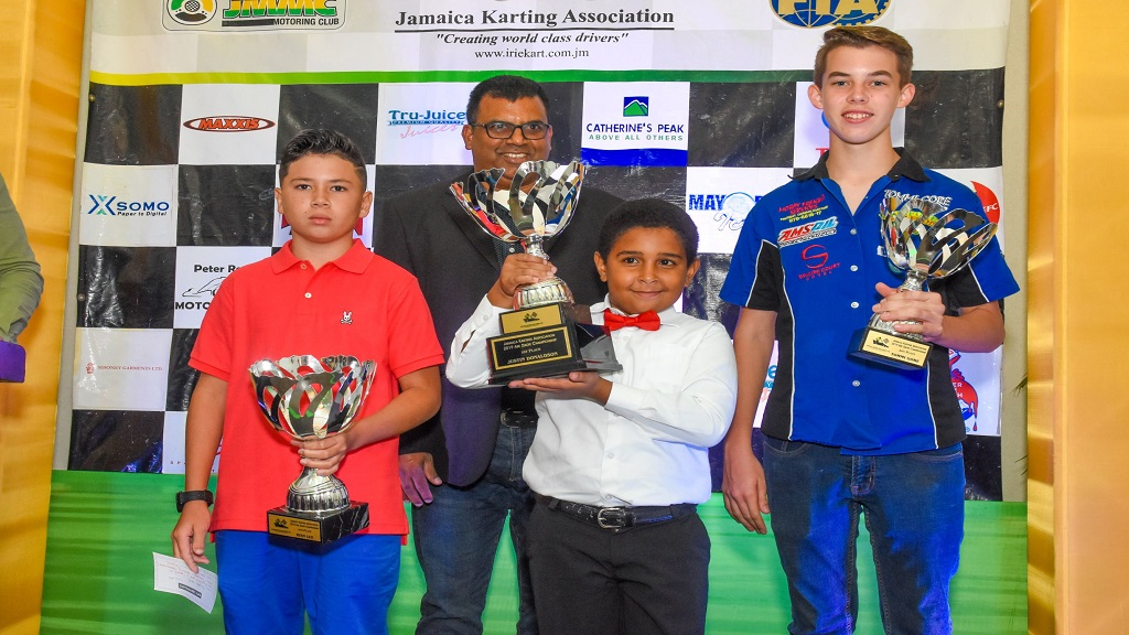 Justin Donaldson (centre) shows off his trophy for the overall Jamaica Karting Association  (JKA) 2019 Abe Ziadie champion at the JKA's annual awards presentation at the Spanish Court Hotel in New Kingston recently. Ryan Lue (left) and Tommi Gore (right) celebrate second and third places, respectively. Sharing in the occasion is Rugie Misir, President of the JKA.
