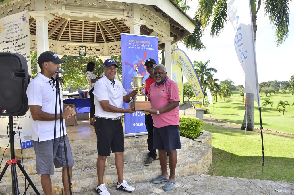 At left Chairman of the Rotary Club of Kingston's Annual Charity Golf Tournament  Committee and  Past President of the club Richard Josephs looks on as Club President Steven Hudson (second left) presents the winner's trophy to Teddy Richards (right). In the background is the club's Immediate Past President and member of the Golf Committee, Linval Freeman.