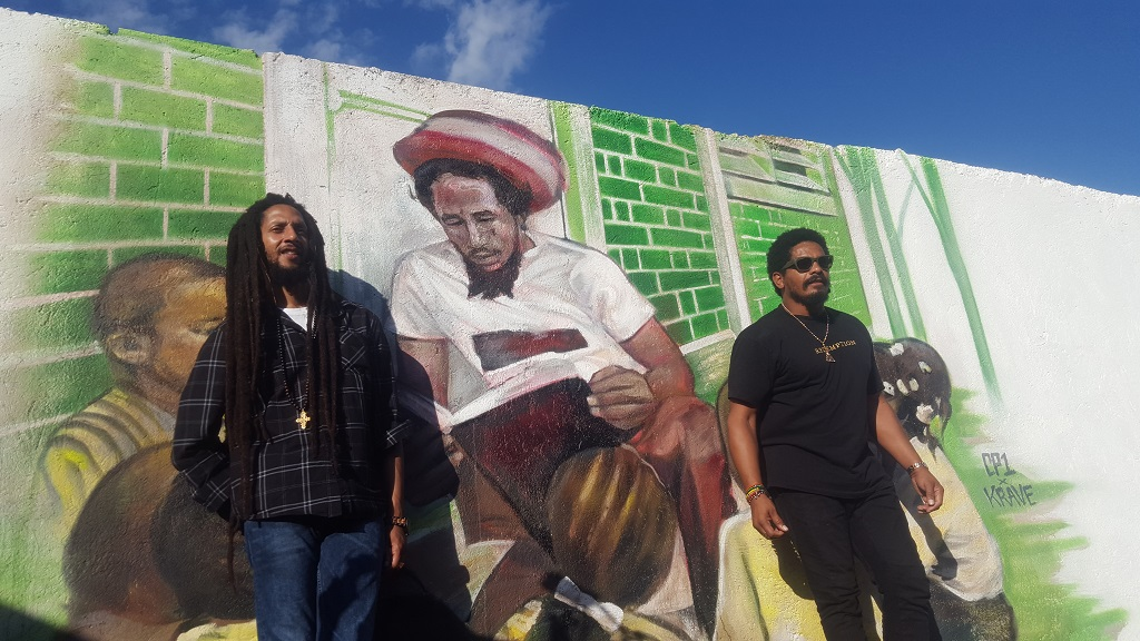 Julian Marley (left) and Rohan Marley pose in front of a mural of their late father, reggae legend Bob Marley, at the Cornerstone Learning Centre in Wilton Gardens. (Photos: Marlon Reid)