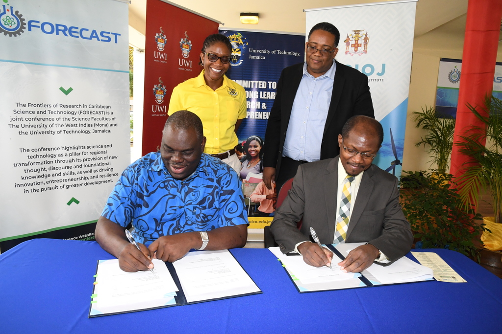 Professor Colin Gyles (seated, right), Deputy President, University of Technology, Jamaica and Donovan Stanberry (seated, left), Campus Registrar, University of the West Indies, Mona, sign a MoU for the Frontiers of Research in Caribbean Science and Technology (FORECAST) Conference scheduled to be held June 9-12. Witnessing the signing are: Professor Michael Taylor (standing, right), Dean, Faculty of Science and Technology at The UWI Kamilah Hylton, Dean, Faculty of Science and Sport at UTech.