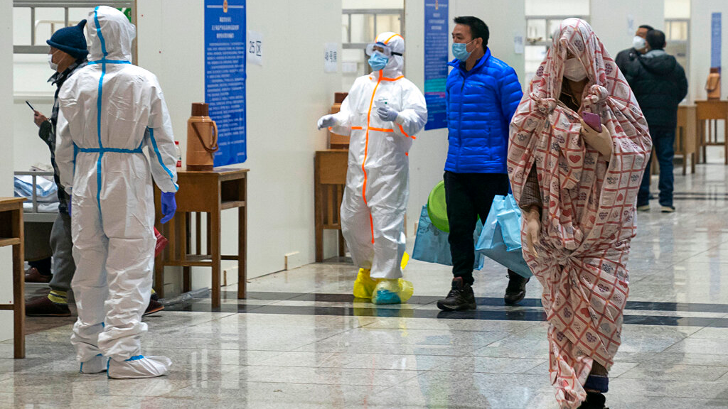 In this Wednesday, February 5, 2020, photo, medical workers in a protective suit help patients who diagnosed with the coronaviruses as they arrive at a temporary hospital which transformed from an exhibition center in Wuhan in central China's Hubei province.  (Chinatopix via AP)