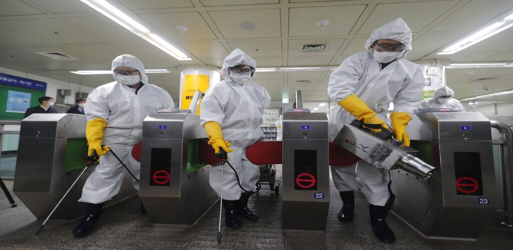 Workers wearing protective gears spray disinfectant as a precaution against the new coronavirus at a subway station in Seoul, South Korea, February, 28.