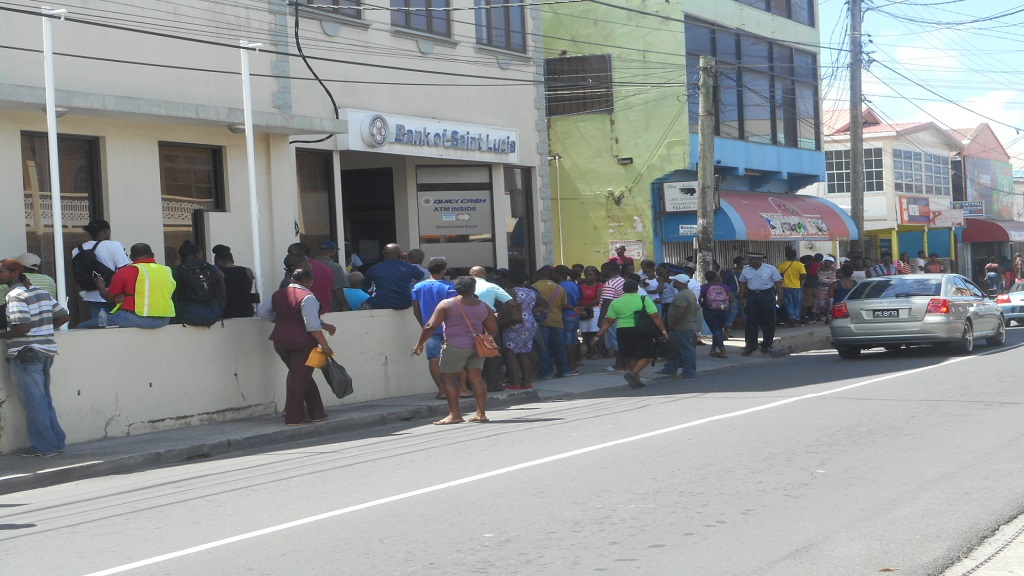 Customers outside Bank of Saint Lucia waiting on their turn to enter the bank