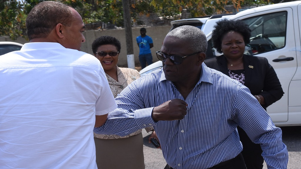 Jamaica's Health Minister, Dr Tufton and Chairman of the South East Regional Health Authority (SERHA), Wentworth Charles, greet each other with an 'elbow bump' at a ceremony last week in Kingston. (Photo: Marlon Reid)