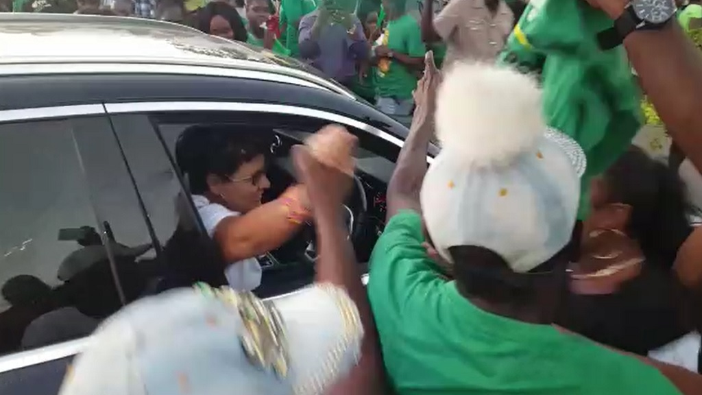 People's National Party's caretaker for South East Clarendon, Patricia Duncan-Sutherland greets JLP supporters as she drives through a sea of 'Labourites' after the closing of polls on Monday.