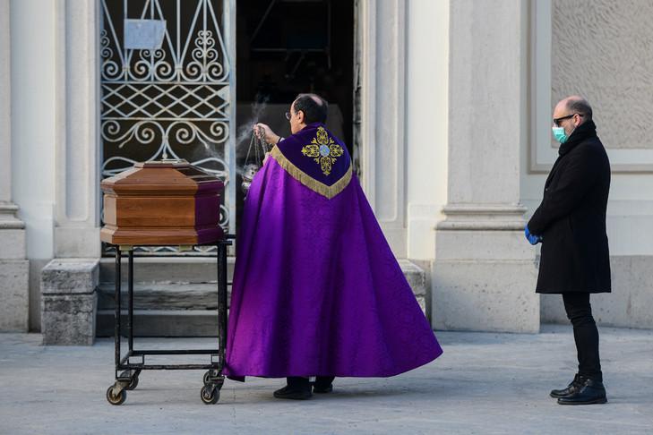 Un fils à côté du cercueil de sa mère lors d'un service funéraire restreint à Seriate, près de Bergame au nord-est de Milan le 20 mars 2020 / AFP