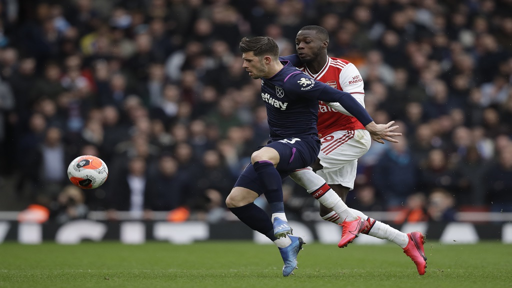 West Ham's Aaron Cresswell, left, vies for the ball with Arsenal's Nicolas Pepe during the Premier League football match  at the Emirates Stadium in London, Saturday, March 7, 2020.(AP Photo/Matt Dunham).