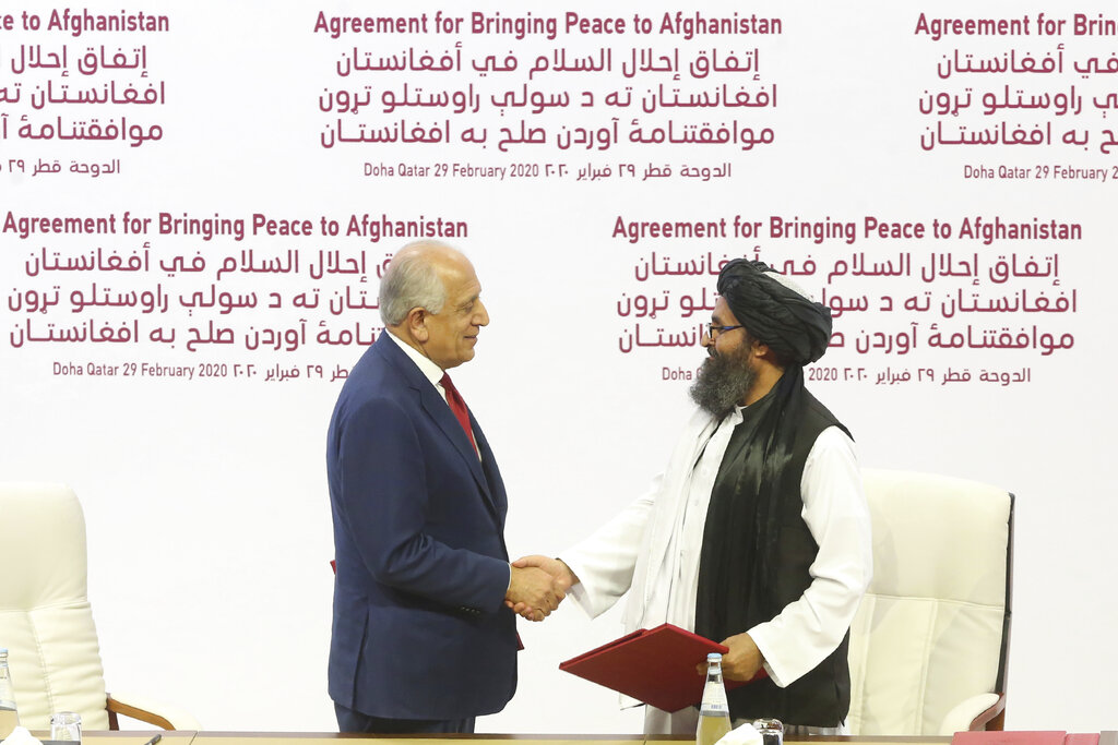 US peace envoy Zalmay Khalilzad, left, and Mullah Abdul Ghani Baradar, the Taliban group's top political leader shack hands after signing a peace agreement between Taliban and US officials in Doha, Qatar, Saturday, February 29, 2020.