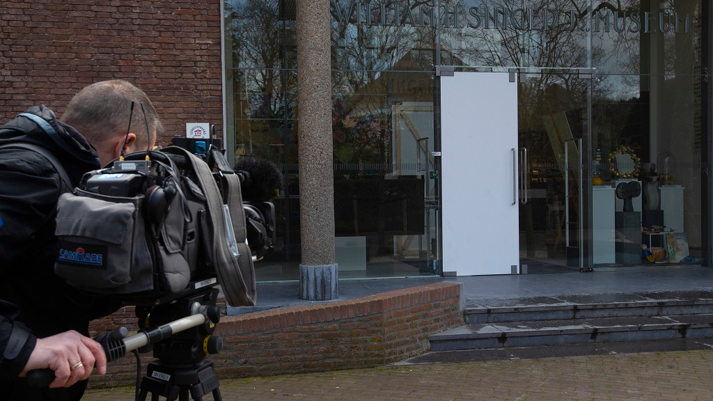 A cameraman films the glass door which was smashed during a break-in at the Singer Museum in Laren, Netherlands,  March 30, 2020. Police are investigating a break-in at a Dutch art museum that is currently closed because of restrictions aimed at slowing the spread of the coronavirus, the museum and police said on March 30. (AP Photo/Peter Dejong)