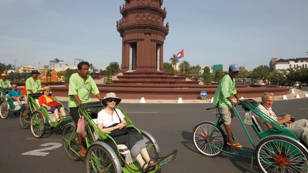 Tourists ride on three-wheeled pedicabs near Independence Monument as they head to Cambodia's Royal Palace in Phnom Penh, Cambodia, Monday, Nov. 5, 2018. (AP Photo/Heng Sinith)