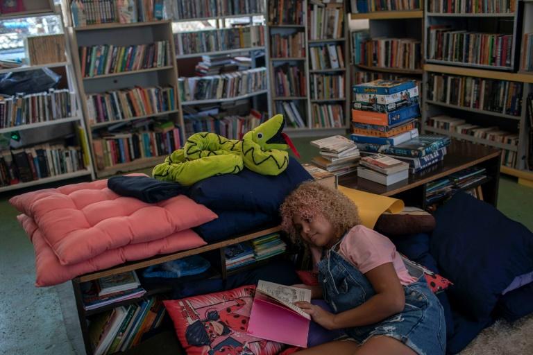 La jeune Brésilienne Lua Oliveira, 12 ans, lit dans la bibliothèque qu'elle a fondée, dans la favela de Tabajaras à Rio de Janeiro, le 10 mars 2020