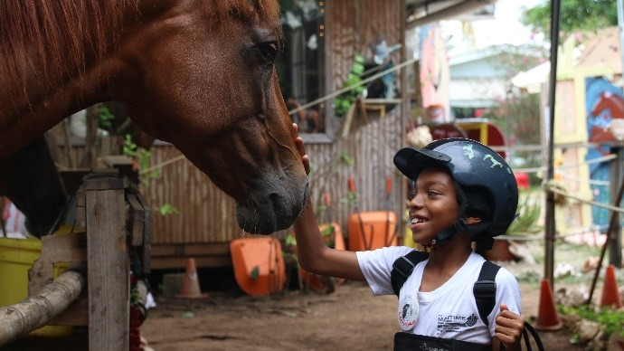 ENT participant, Christiano (11 years old), diagnosed with Cerebral Palsy, building a connection with the equine, Apollo.