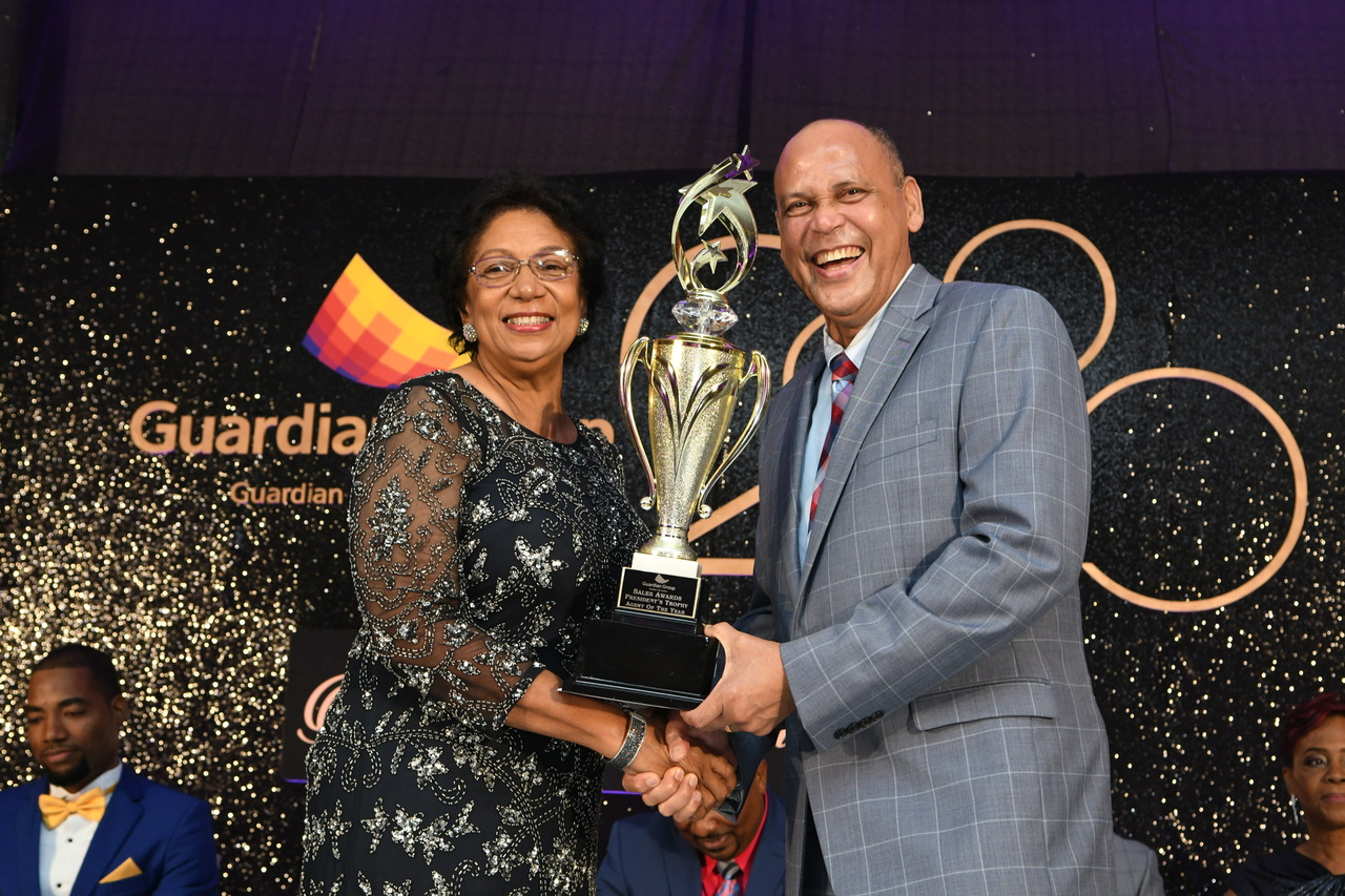 Fay Hutchinson (left) accepts the Chairman's Trophy from Eric Hosin, president of Guardian Life Limited, after copping the Top Sales Advisor of the Year Award at the company's recent Annual Awards, held at the Jamaica Pegasus Hotel.