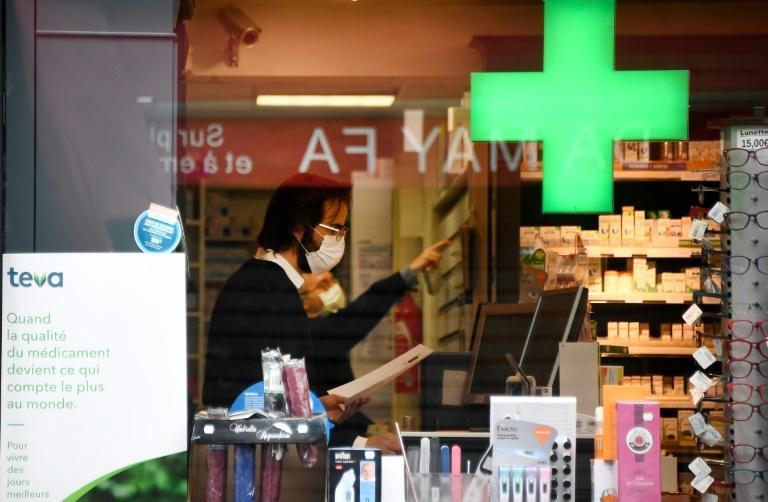 Un pharmacien équipé d'un masque de protection, le 21 mars 2020 à Paris afp.com - FRANCK FIFE