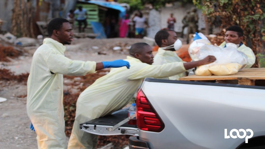 Social workers prepare to deliver food items to residents of Seven Miles last Saturday. (Photo: Marlon Reid)