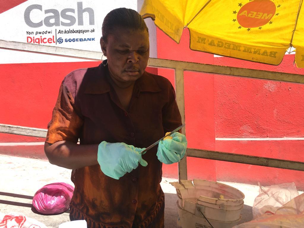 Marlène, la marchande de fruits épluchant un ananas lundi 16 mars 2020. Crédit photo: Eberline Nicolas/Loop Haïti