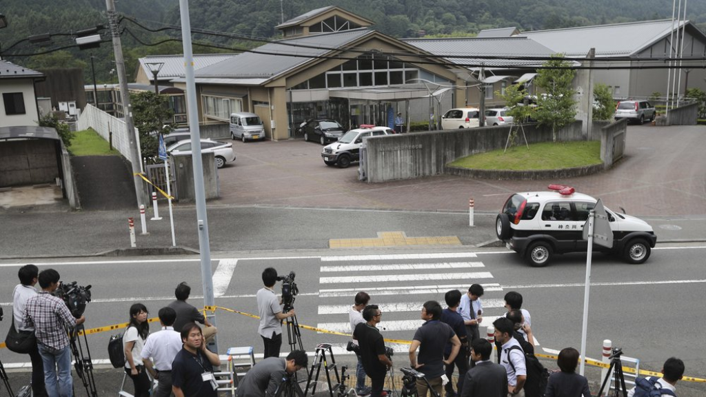 FILE - In this July 26, 2016, file photo, journalists gather in front of Tsukui Yamayuri-en, a facility for the handicapped where a former care home employee killed disabled people, in Sagamihara, outside Tokyo. The Yokohama District Court sentenced Satoshi Uematsu, 30, to death Monday, March 16, 2020, for killing 19 disabled people and injuring 24 others four years ago in the deadliest mass attack in postwar Japan. (AP Photo/Eugene Hoshiko, File)