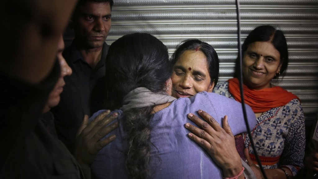 Asha Devi, mother of the victim of the fatal 2012 gang rape on a moving bus, facing camera, is embraced by an unidentified woman after the rapists of her daughter were hanged in New Delhi, India, Friday, March 20, 2020. Four men were sentenced to capital punishment for the 2012 gang-rape of a 23-year-old physiotherapy student on a moving bus in New Delhi have been executed. (AP Photo/Altaf Qadri)