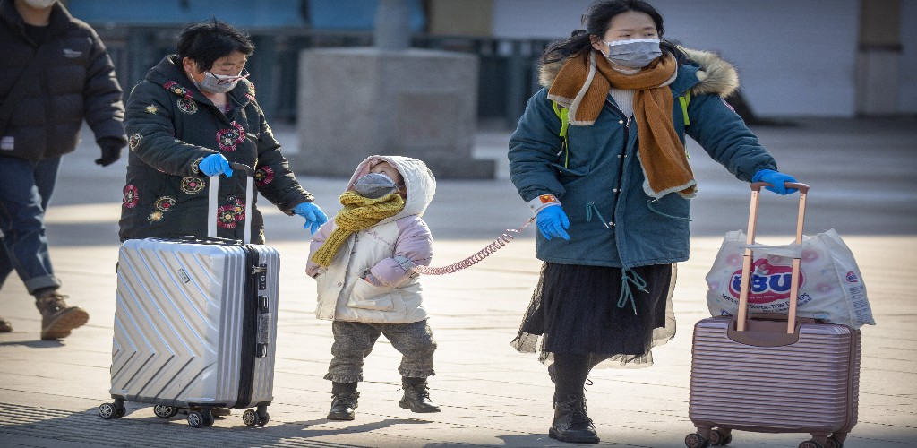 Travelers wear face masks as they walk outside the Beijing Railway Station in Beijing, Saturday, February 15, 2020. People returning to Beijing will now have to isolate themselves either at home or in a concentrated area for medical observation, said a notice from the Chinese capital's prevention and control work group published by state media late Friday. (AP Photo/Mark Schiefelbein)