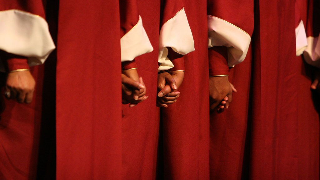 iStock photo of members of a choir holding hands.