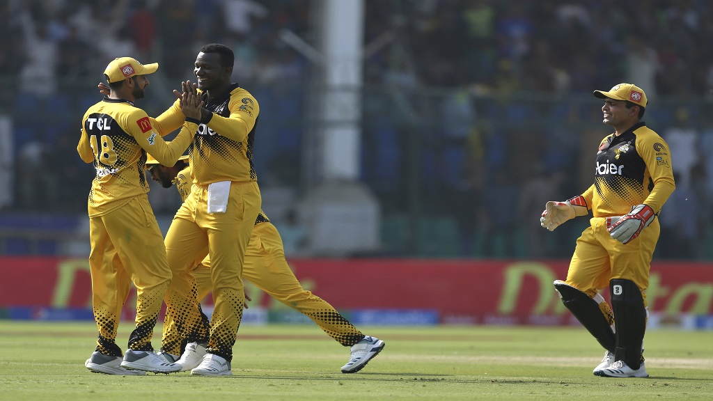 Peshawar Zalmi's Daren Sammy, centre, celebrates with teammates after taking the wicket of Quetta Gladiator's batsman Safraz Ahmed during the Pakistan Super League T20 cricket match against Quetta Gladiators at the National stadium in Karachi, Pakistan, Saturday, Feb. 22, 2020. (AP Photo/Fareed Khan).