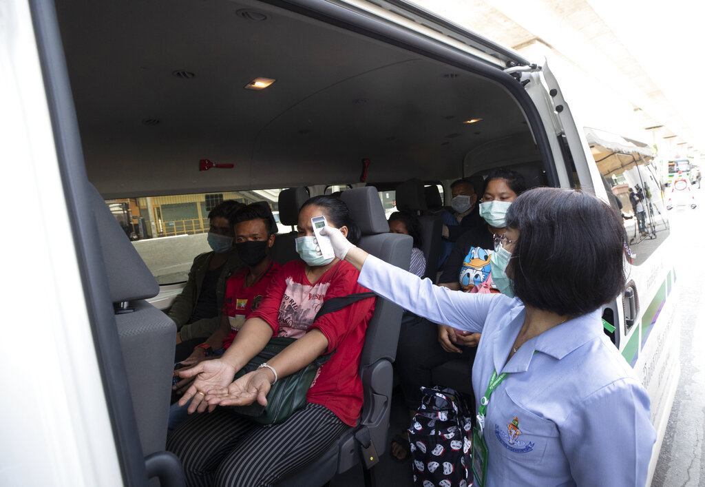 Health officer check temperature passenger in van at a health check point in Bangkok, Thailand, Thursday, March 26, 2020. (AP Photo/Sakchai Lalit)