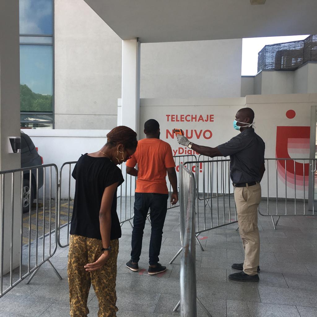 Un agent de sécurité prend la température des visiteurs, se distançant d'un 1m50, à la centrale de Digicel à Turgeau ce vendredi 27 mars 2020 Crédit photo/Luckenson Jean/LoopHaïti