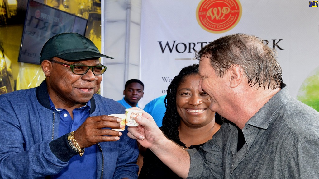 Tourism Minister, Edmund Bartlett (left), shares a toast with Managing Director, J Wray and Nephew, Jean-Phillipe Beyer (right), on Saturday's opening day of the two-day Jamaica Rum Festival at Hope Gardens in St Andrew. Sharing the moment is Senior Director, Public Affairs, J Wray and Nephew, Tanikie McClarthy Allen (centre).