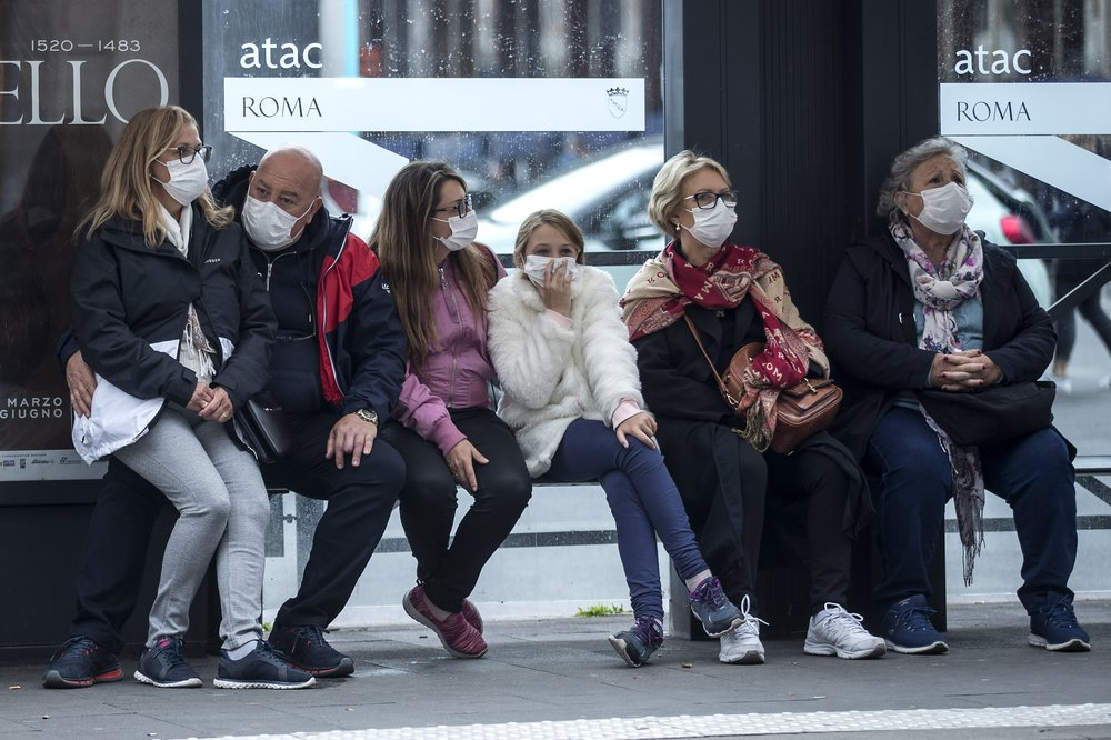 People wait at a bus stop, in Rome, Monday, March 9, 2020. Italy announced a sweeping quarantine early Sunday for its northern regions, igniting travel chaos as it restricted the movements of a quarter of its population in a bid to halt the new coronavirus' relentless march across Europe. (Roberto Monaldo/LaPresse via AP)
