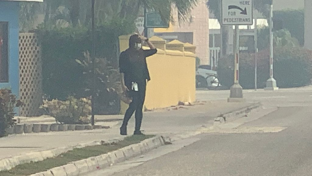 A pedestrian at the intersection by Kirks with a face mask and appearing to be in discomfort from the smoke