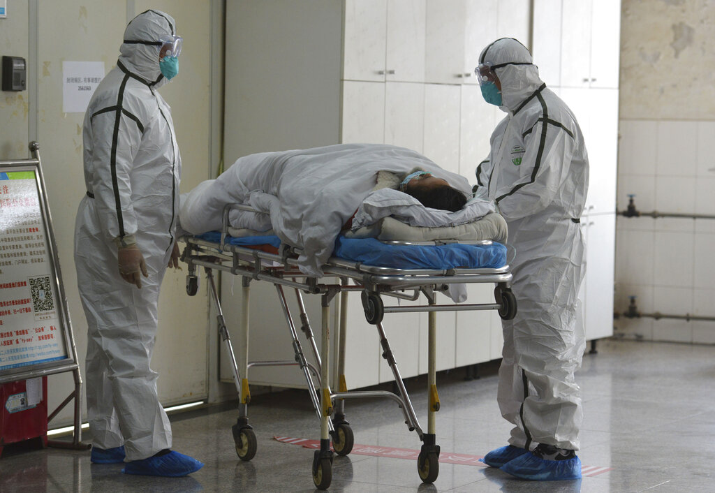Medical workers in protective suits move a coronavirus patient into an isolation ward at the Second People's Hospital in Fuyang in central China's Anhui Province, Saturday, Feb 1, 2020.