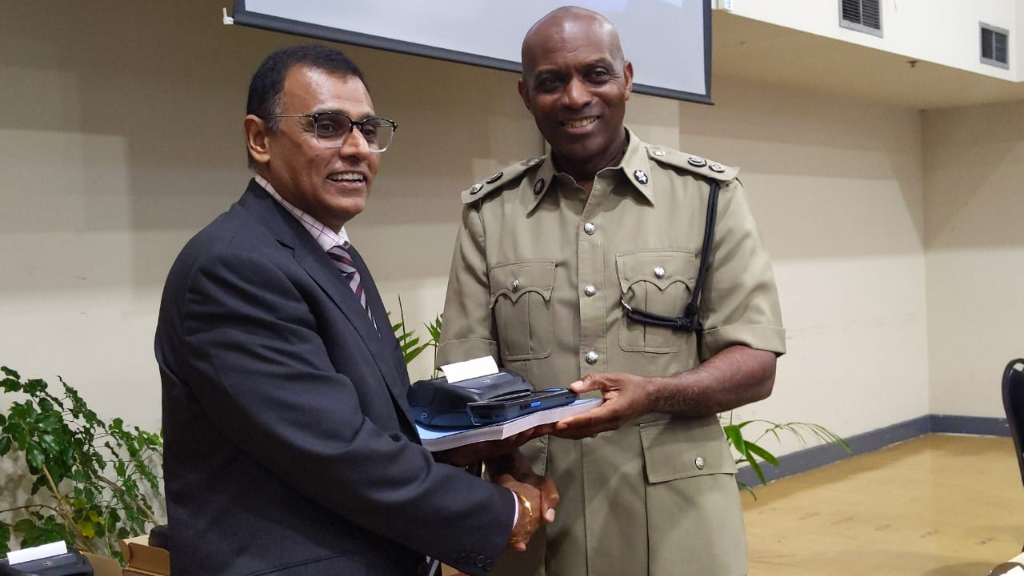 Minister of Works and Transport, Rohan Sinanan (left) hands over one of the new ticketing devices to DCP Jayson Forde.
