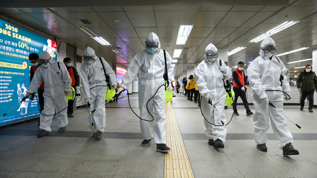Workers wearing protective gears disinfect as a precaution against the new coronavirus at the subway station in Seoul, South Korea, Wednesday, March 11, 2020. (Kim Sun-woong/Newsis via AP)