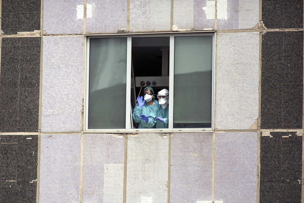 FILE, in this Wednesday, March 18, 2020 file photo, medical workers wearing face masks gesture from hospital La Paz in Madrid, Spain. (AP Photo/Manu Fernandez, File)