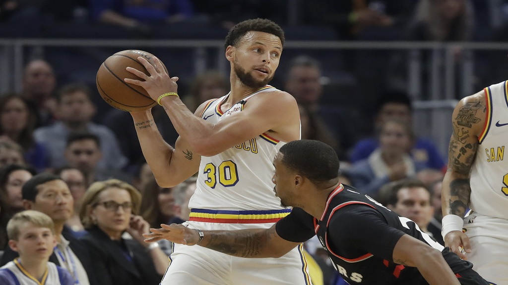 Golden State Warriors guard Stephen Curry (30) looks to pass over Toronto Raptors guard Norman Powell during the first half of an NBA basketball game in San Francisco, Thursday, March 5, 2020. (AP Photo/Jeff Chiu).