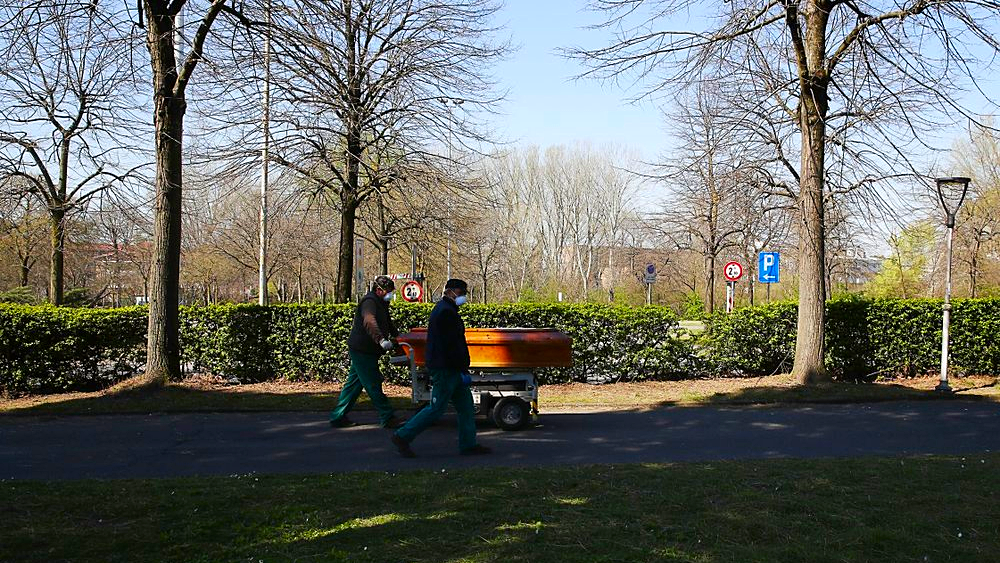 Two men carry a coffin to the Melegnano cemetery's morgue, outskirts of Milan, Italy, Tuesday, March 24, 2020. For most people, the new coronavirus causes only mild or moderate symptoms. For some it can cause more severe illness, especially in older adults and people with existing health problems. (AP Photo/Antonio Calanni)