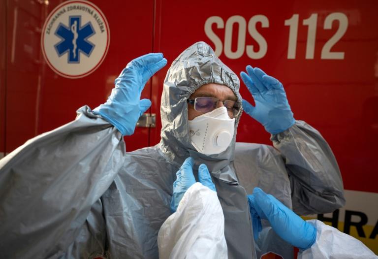 Un membre du personnel soignant revêt sa tenue de protection avant de s'occuper de malades, à Bratislava, en Slovaquie, le 16 mars 2020