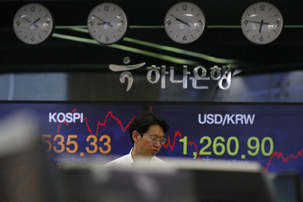 A currency trader walks by screens showing the Korea Composite Stock Price Index (KOSPI), left, and the foreign exchange rate between US dollar and South Korean won at the foreign exchange dealing room in Seoul, South Korea, Tuesday, March 24, 2020. (AP Photo/Lee Jin-man)