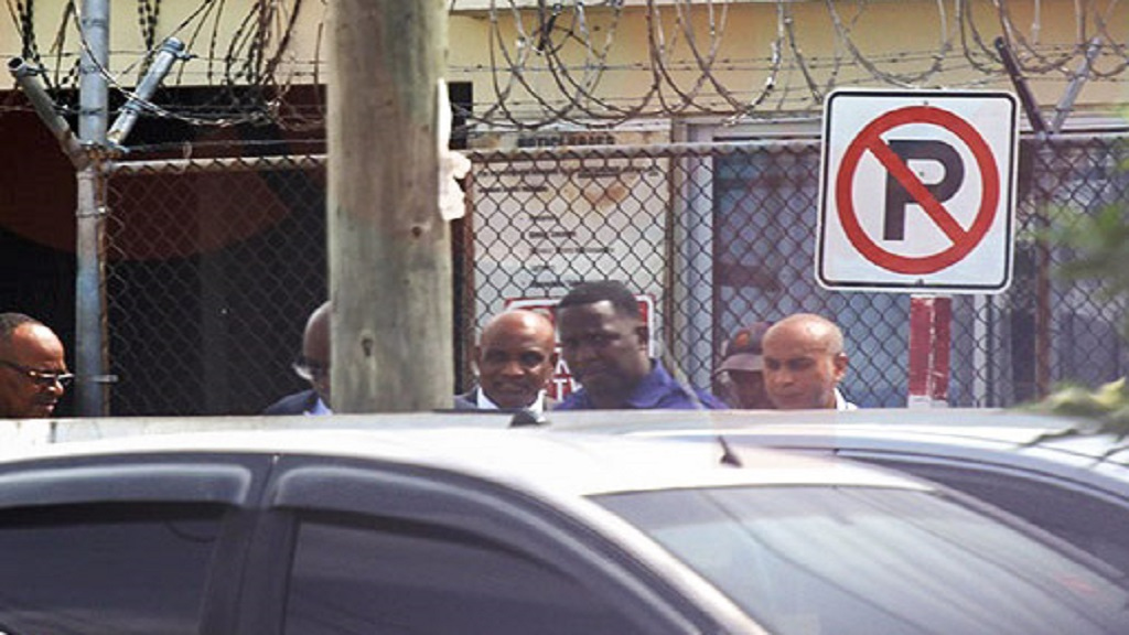 Former Education Minister Ruel Reid (partially hidden, second left) and CMU President, Professor Fritz Pinnock (centre) being escorted to a motor vehicle outside the Half-Way Tree Police Lock-up on Thursday morning. (PHOTO: Julian Richardson)