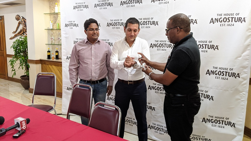 Photo L-R: Rahim Mohammed, Angostura's Executive Manager, Marketing Services, Chairman Terrence Bharath and Ian Forbes, Executive Manager, Operations, display a sample of the sanitiser liquid which the company is making to be donated to emergency responders.