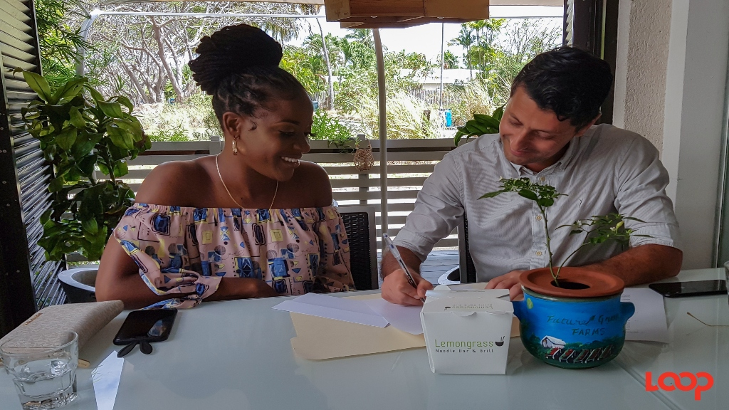Faith Callender and Lemongrass owner, Saman Golesorkhi, signing her contract.