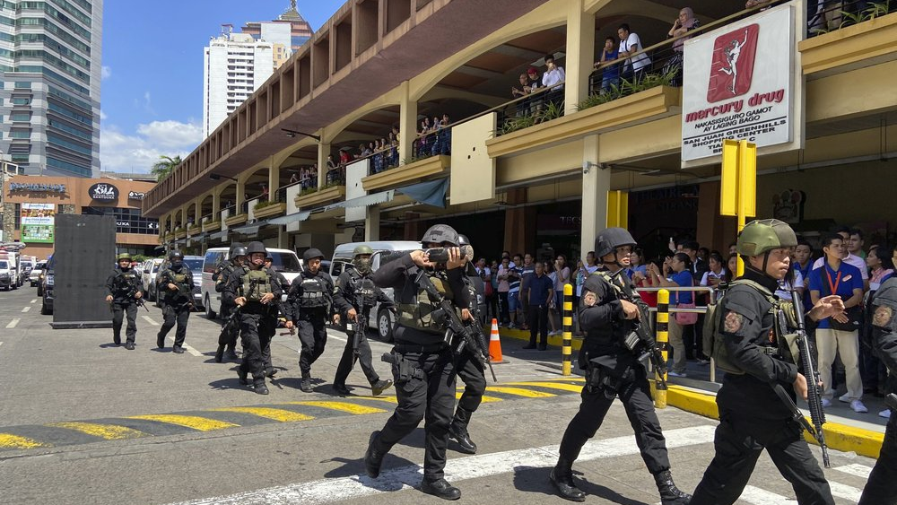 A group of armed police arrive at the Greenhills Shopping Center Monday, March 2, 2002, in Manila, Philippines. Philippine police on Monday surrounded a shopping mall in an upscale district in the Manila metropolis after gunshots rang out inside and sent shoppers rushing out in panic. (AP Photo/Aaron Favila)