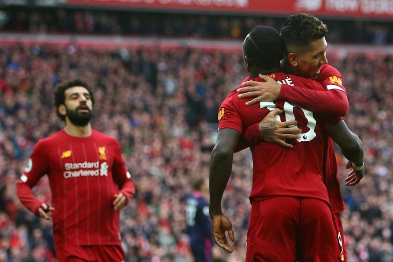 L'attaquant sénégalais de Liverpool Sadio Mane célébre la victoire de son équipe face à Bournemouth avec ses coéquipiers Roberto Firmino et Mohamed Salah le 7 mars 2020 à Liverpool