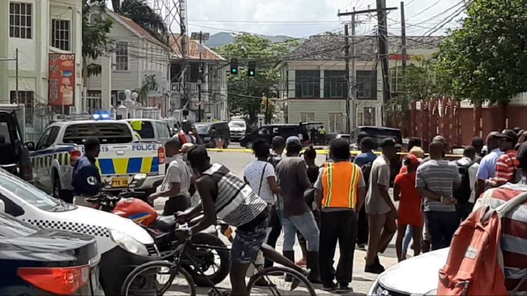 Police personnel and curious onlookers at the scene of the murder of a Chinese businessman in Montego Bay on Monday.